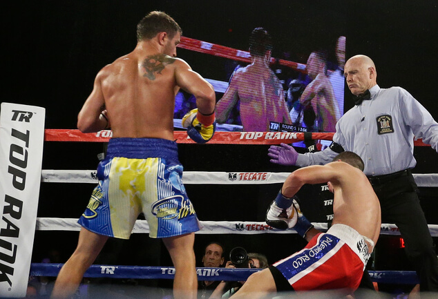 Vasyl Lomachenko, left, of Ukraine, knocks down Roman Martinez, of Puerto Rico, during the fifth round of a WBO junior lightweight title boxing match Saturday, June 11, 2016, in New York. Lomachenko stopped Martinez in the fifth round. (AP Photo/Frank Franklin II)